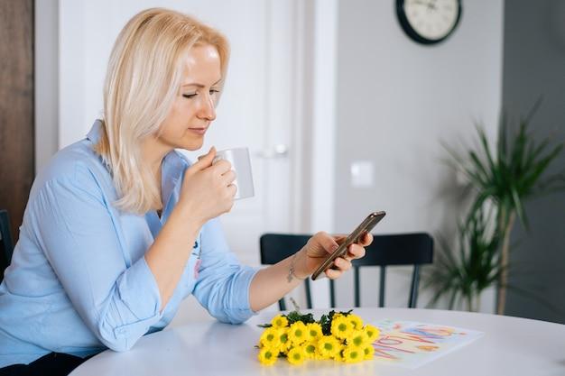 앉아있는 동안 휴대폰을 사용하고 커피를 마시는 아름다운 금발의 젊은 여성의 초상화