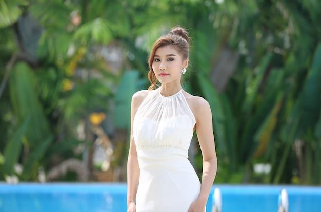Портрет красивой невесты в свадебном платье с длинной пышной юбкой, невеста в парке - красивое длинное свадебное платье.
