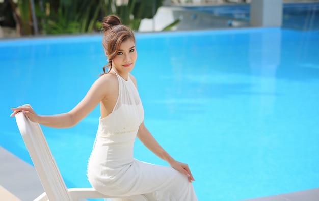Портрет красивая невеста в свадебном платье с длинной пышной юбкой, сидя у бассейна.