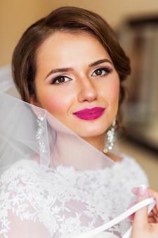밝은 하얀 웨딩 드레스에 아름 다운 신부의 초상화를 확인합니다. 결혼식을위한 신혼 여성 최종 준비입니다.