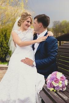 Портрет красивой невесты, сидящей с женихом на скамейке в парке