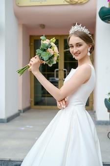 コロネットと美しい花嫁の肖像画は屋外の手で花の花束を保持します