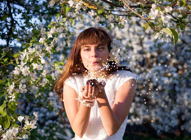 花のリンゴの木公園で花びらに吹く美しいブルネットの肖像画。調和、平和、静けさのコンセプト。