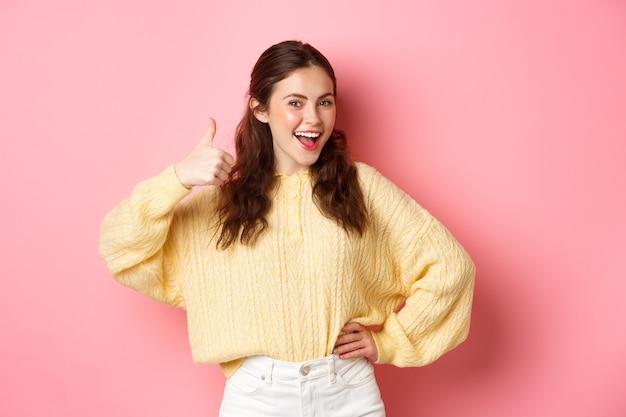 ピンクの壁に立って、あなたのアイデアのように、親指を立てて見せている美しいブルネットの女性モデルの肖像画は、何か良いものをサポート、承認、または賞賛します。