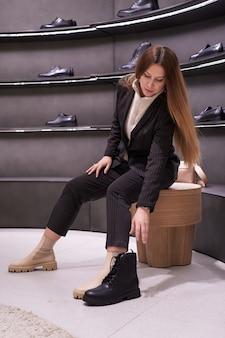 아름 다운 갈색 머리 여자의 초상화가 게에서 신발을 선택