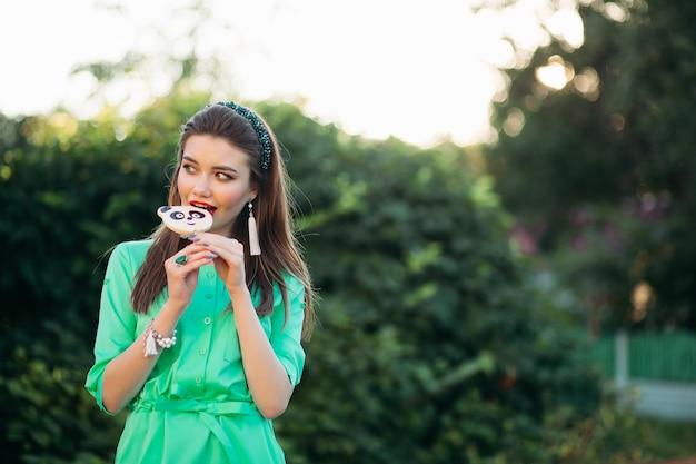 Портрет красивая брюнетка девушка в зеленом платье, едят конфеты, как панда.