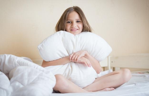 침대에 앉아 하얀 베개를 껴안고 아름다운 갈색 머리 소녀의 초상화