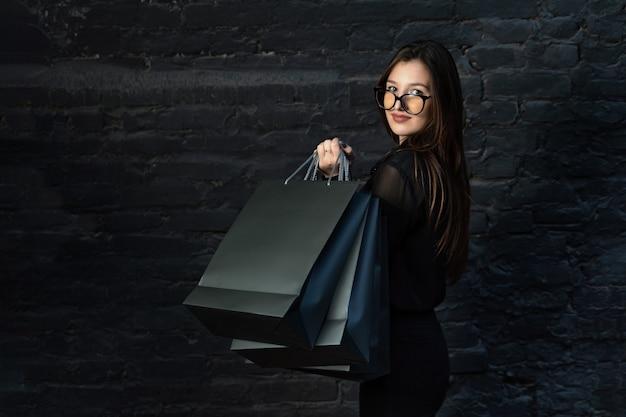 검은 쇼핑백과 아름 다운 갈색 머리 여자의 초상화