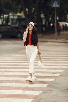 Портрет красивой брюнетки. модель в летнем городе. женщина ходит с мобильным телефоном.
