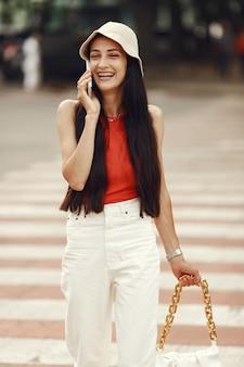 美しいブルネットの肖像画。夏の街のモデル。女性は携帯電話で歩きます。