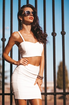 夏の白いタンクトップとスカートの美しいブルネットモデルの肖像画。女性が鉄の柵の近くの通りでポーズします。サングラスの女性
