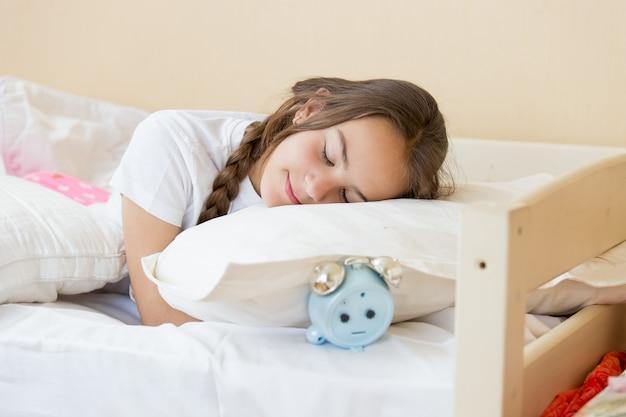 Портрет красивой девочки-подростка брюнетки, спать на подушке будильника