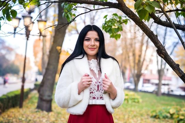 秋の公園の毛皮のジャケットで美しいブルネットの女性の肖像画