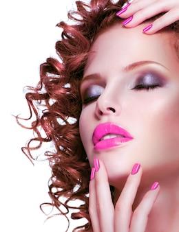 明るいメイクとマニキュアで美しいブルネットの女性の肖像画。白で隔離の巻き毛の髪型のクローズアップの顔。