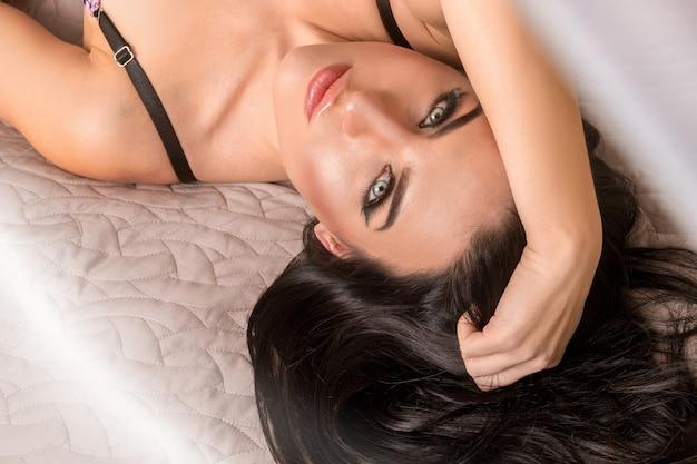 正面を見てベッドで素敵な化粧をした美しいブルネットの女性の肖像画
