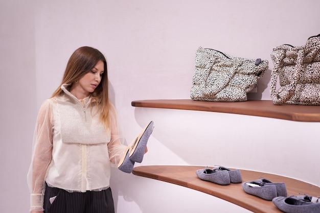아름 다운 갈색 머리 젊은 여자의 초상화는 가게에서 신발을 선택