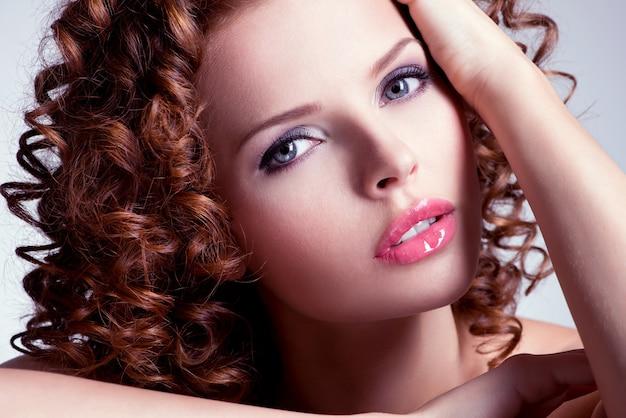 밝은 메이크업과 아름 다운 갈색 머리 젊은 여자의 초상화. 곱슬 헤어 스타일을 가진 근접 촬영 얼굴입니다.