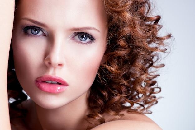 Портрет красивой молодой женщины брюнет с ярким составом. лицо крупного плана с вьющейся прической.