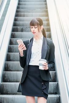 Портрет красивой деловой женщины, использующей смартфон в эскалаторе по пути на работу