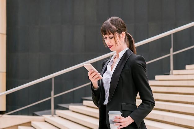 Портрет красивой деловой женщины с помощью смартфона по дороге на работу