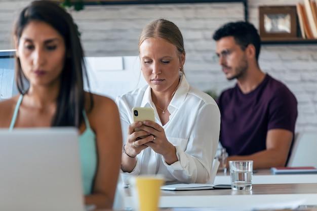 オフィスで働いている間彼女の携帯電話を使用して美しいビジネスの若い女性の肖像画。