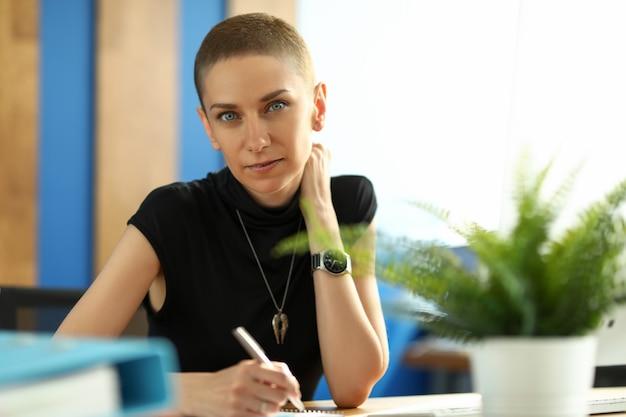 銀のペンを押しながら紙にメモを作る美しい実業家の肖像画。黒のドレスの若い女性。テーブルの上の緑の植物。