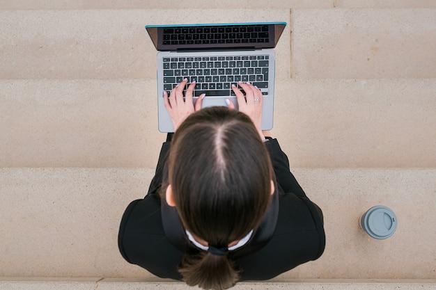 Портрет красивой деловой женщины, использующей ноутбук, сидя на лестнице на городской улице