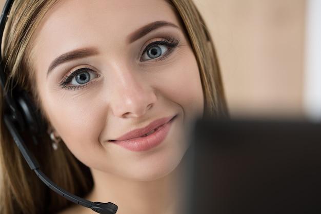 Портрет оператора красивого call-центра на работе. женщина с гарнитурой разговаривает с кем-то в интернете