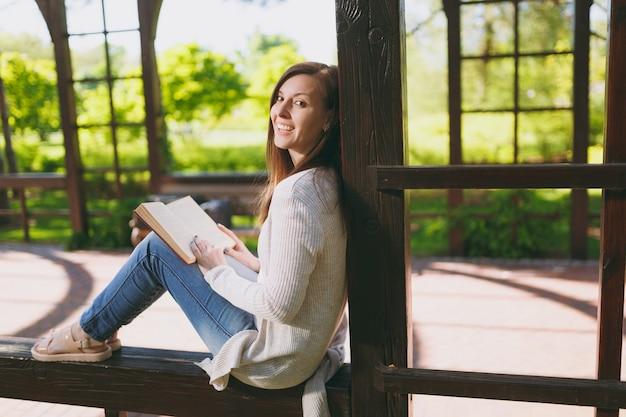 軽いカジュアルな服、ジーンズ、リラックスして、本を読んで身に着けている美しい穏やかな平和な若い女性の肖像画。春の自然の屋外通りの都市公園で休んでいる女性の笑顔。ライフスタイルのコンセプト。