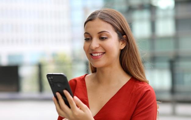 バックグラウンドで近代的な高層ビルと携帯電話のチャットアプリでメッセージを送信する美しいカジュアルなビジネス女性の肖像画
