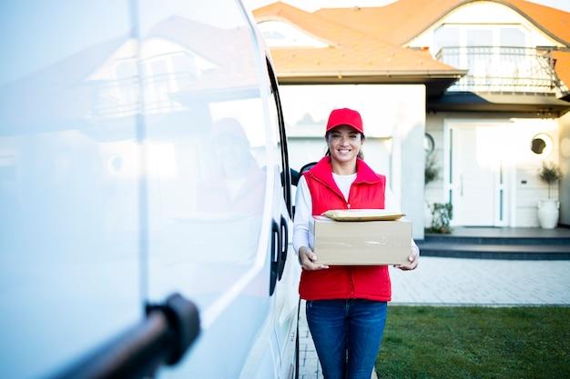 Портрет красивой кавказской женщины-курьера, держащей посылки на своем фургоне, готовые к доставке.