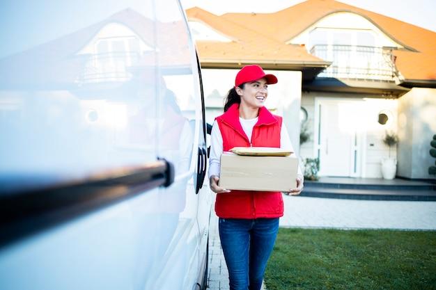 Портрет красивой кавказской работницы службы доставки, держащей посылки ее фургоном, готовым доставить.