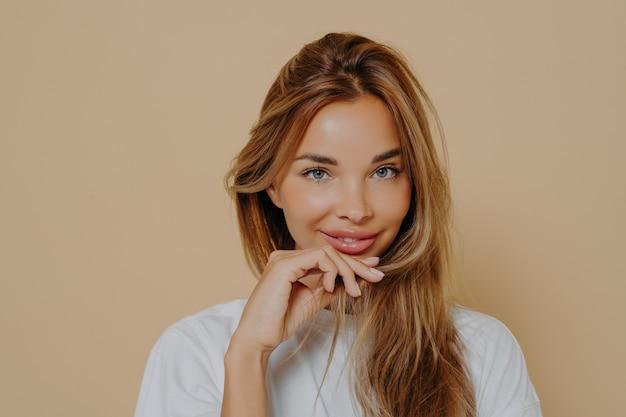 Портрет красивой кавказской девушки в белой футболке, с красивой улыбкой смотрящей в камеру