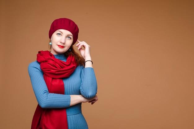 青いドレス、赤い帽子、赤いスカーフのミディアム黒髪の美しい白人女性の肖像画