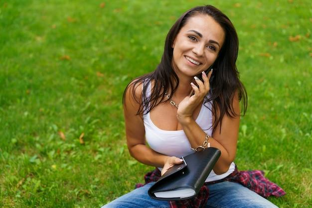 웃고 있는 아름다운 백인 여학생의 초상화는 푸른 잔디에 앉아서 열린 전화 통화를 하고 있습니다.