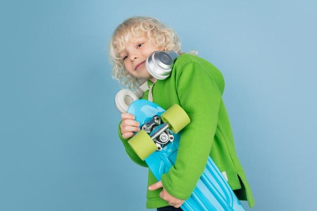 Портрет красивого кавказского маленького мальчика изолированного на голубой предпосылке студии. блондинка кудрявая мужская модель. концепция выражения лица, человеческие эмоции, детство, реклама, продажи.
