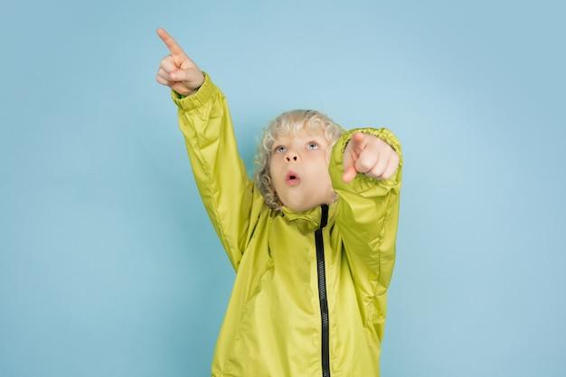블루 스튜디오 배경에 고립 된 아름 다운 백인 어린 소년의 초상화. 금발 곱슬 남성 모델. 표정, 인간의 감정, 어린 시절, 광고, 판매의 개념.