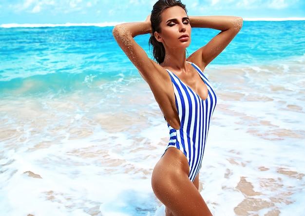 Портрет красивой кавказской загорелой женщины модель с темными длинными волосами в полосатом купальнике позирует на пляже летом с белым песком