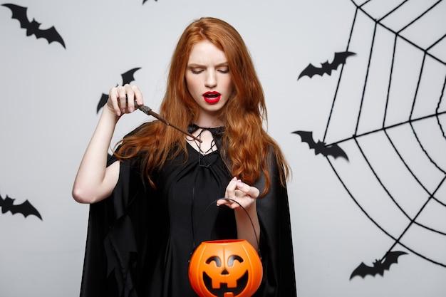 Портрет красивой кавказской ведьмы, держащей оранжевую тыкву для празднования хэллоуина.
