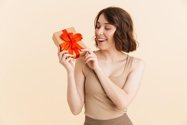 Портрет красивой кавказской женщины 20-х годов, одетой в повседневную одежду, улыбающуюся, держа подарочную коробку изолированной