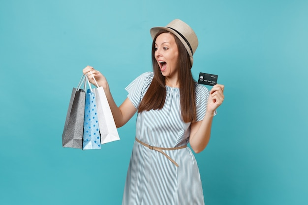 여름 드레스를 입은 아름다운 백인 여성의 초상화, 쇼핑 후 구매한 패키지 가방을 들고 밀짚 모자, 파란색 파스텔 배경에 고립 된 은행 신용 카드. 광고 공간을 복사합니다.