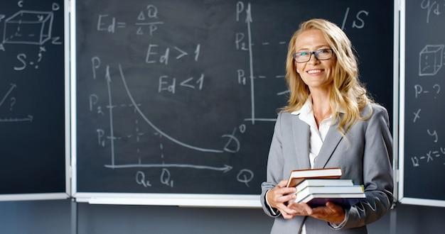 보드에 교실에 서, 카메라에 웃 고 교과서를 들고 아름 다운 백인 여자 선생님의 초상화. 수학 공식 및 도면 칠판에 책을 여성 강사.
