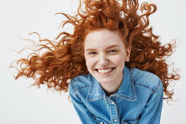 Портрет красивой веселый рыжий женщина с развевающимися вьющимися волосами, улыбаясь смеется