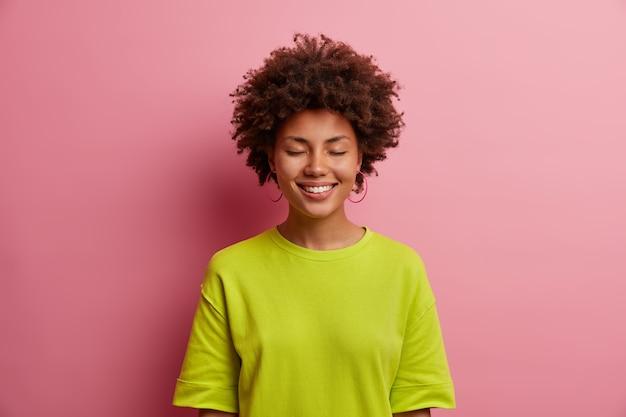 아름 다운 쾌활 한 여자의 초상화는 기쁨과 함께 눈과 미소를 닫고, 캐주얼 녹색 티셔츠를 입고, 분홍색 벽에 격리 된 지원의 즐거운 말을 듣습니다. 행복한 감정과 감정