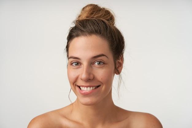 Портрет красивой жизнерадостной женщины без макияжа, позирующей на белом с широкой улыбкой и кусающей нижнюю губу