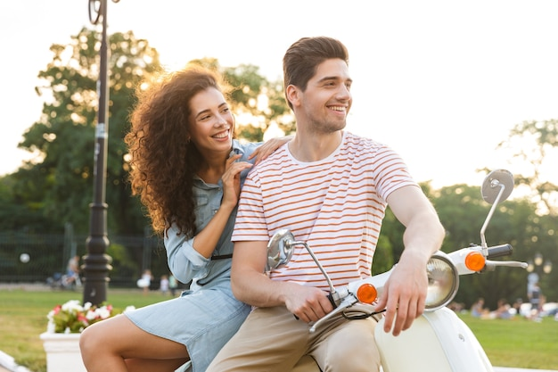 都市公園でバイクに一緒に座って、美しいカップルの肖像画