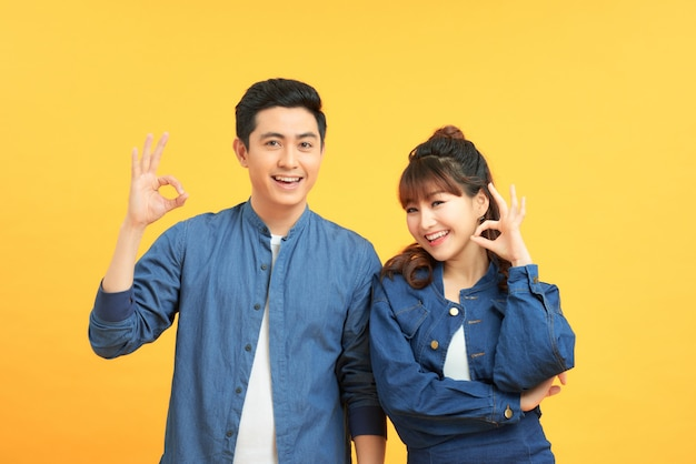 Портрет красивой пары, стоящей вместе, пока женщина обнимает мужчину и показывает знак ок на желтом фоне