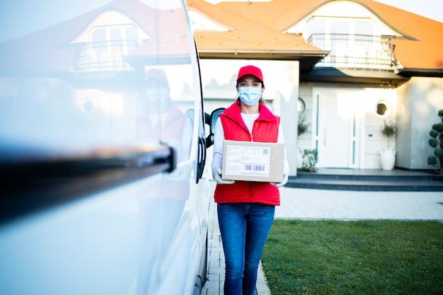 Портрет красивой курьера, держащего посылки у своего фургона, готовые доставить во время пандемии covid19