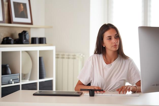 ホームオフィスで働く美しい白人写真家の女性の肖像画