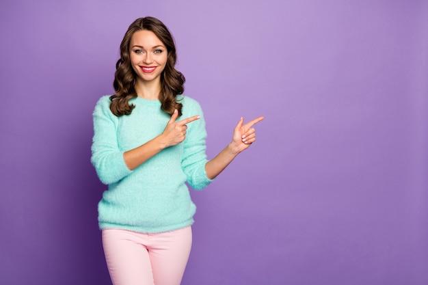 멋진 검은 금요일 쇼핑 가격을 조언하는 손가락 빈 공간을 나타내는 아름다운 곱슬 아가씨의 초상화 캐주얼 청록색 푹신한 풀오버 핑크 바지를 착용하십시오.